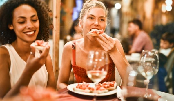 2 women enjoying food and wine