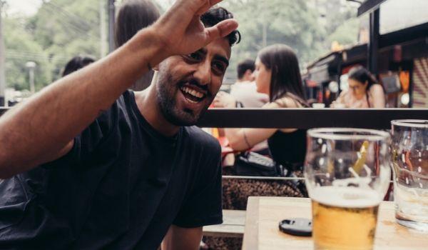 Happy guy drinking outside